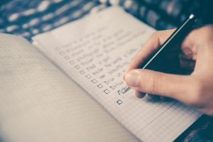 A hand holding a pen, writing a checklist in a notebook